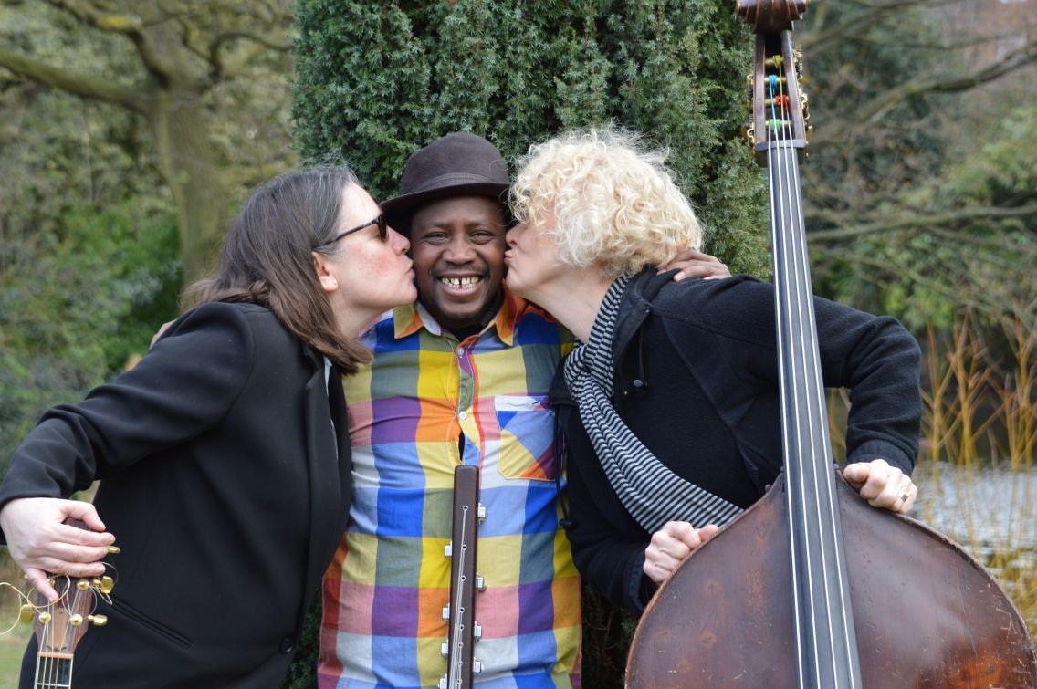 Caroline Trettine and Alison Rayner flanking and kissing kora player Mosi Conde