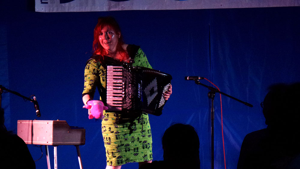 Hattie Hatstar squeezing her accordian in a lovely green dress